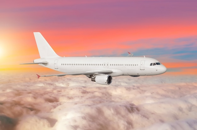 Flying airplane above the clouds horizon sky with bright sunset colors.