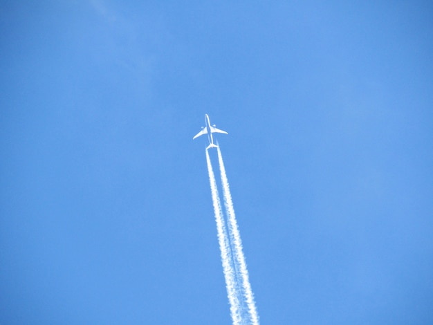 Flying airplane with air trail stripes