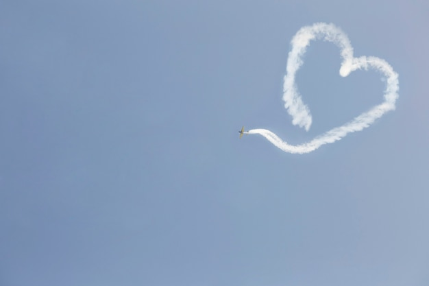 A flying airplane with smoke in the form of a heart. valentine's day.