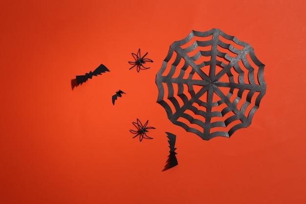 주황색 밝은 배경에 날아다니는 박쥐, 거미, 거미줄. 할로윈 배경입니다. 평면도. 플랫 레이