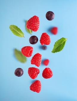 Летающие ягоды на синем столе. падающие плоды малины и мяты