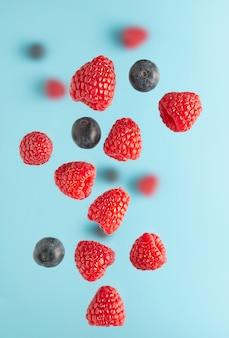 Летающие ягоды над синим столом. падающие ягоды, такие как малина и черника