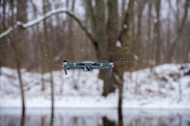Flying black drone during winter