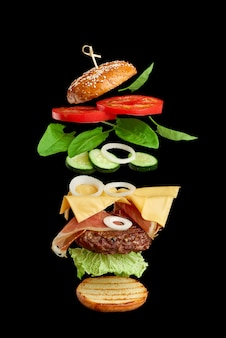 Flying burger ingredients: cutlet, sesame seed bun, tomato, onion, green lettuce, cheese on black
