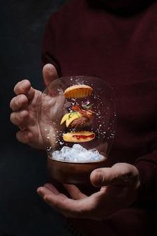 남자의 손에 비행 햄버거 장난감. 눈이 내리는 공