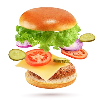 Flying burger with beef patty, cheese, pickles, tomato, onion and lettuce isolated on white background