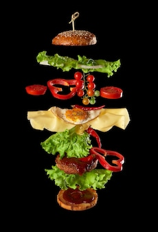 Flying cheeseburger ingredients: meat cutlet, sesame loaf, cheese, fried egg, tomato and green lettuce on black background