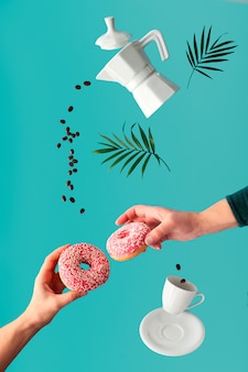 Flying coffee beans. ceramic coffee maker and espresso cup. vibrant, trendy, bold green mint color wall with palm leaves. surreal levitation with coffee, two pink doughnuts in female hands