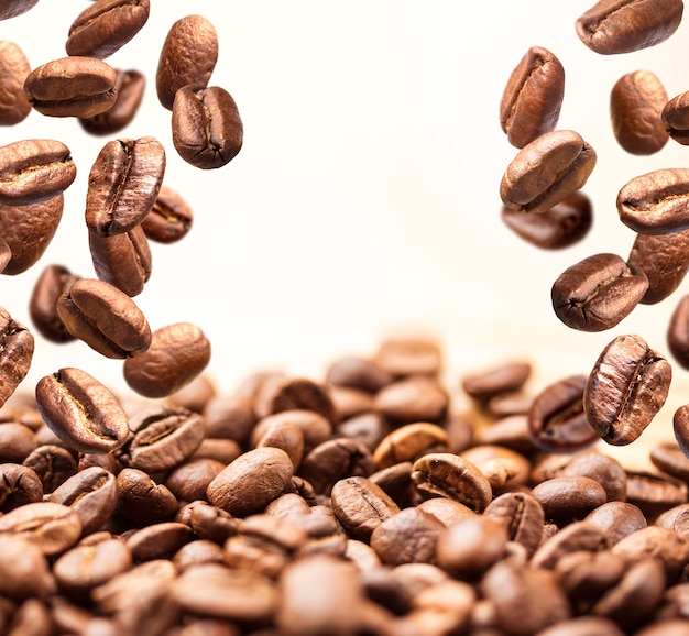 Flying coffee beans on white