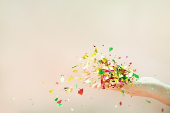 Flying colorful confetti from hand on beige background
