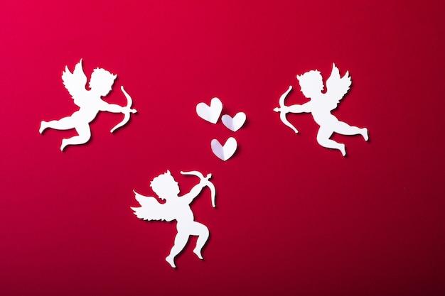空飛ぶキューピッドのシルエット、幸せなバレンタインデーのバナー、ペーパーアートスタイル。赤い紙に情事