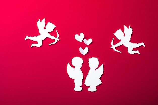 空飛ぶキューピッドのシルエット、2つの白い天使、幸せなバレンタインデーのバナー、ペーパーアートスタイル。赤い紙に情事