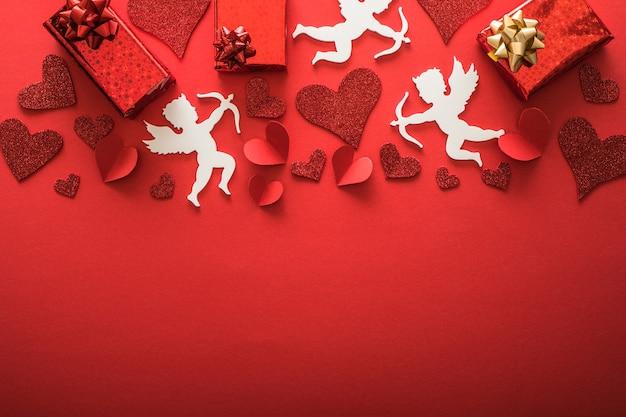 ハート、ギフト、幸せなバレンタインデーのバナー、ペーパーアートスタイルの空飛ぶキューピッドシルエット。赤い紙に情事