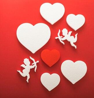 ハート、幸せなバレンタインデーのバナー、ペーパーアートスタイルの空飛ぶキューピッドシルエット。赤い紙に情事