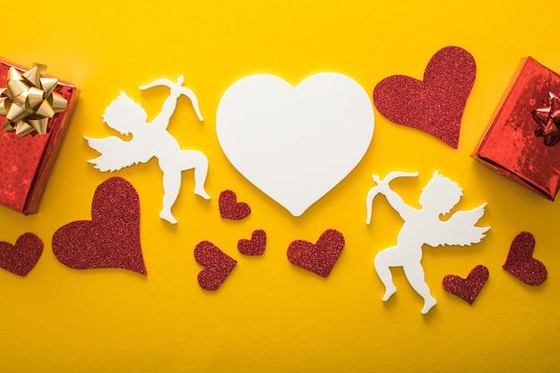 ハート、幸せなバレンタインデーのバナー、ペーパーアートスタイルの空飛ぶキューピッドシルエット。黄色い紙に情事
