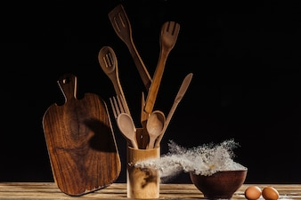 Flying cutting board, kitchen utensils, flour from bowl and two eggs on table on black bac
