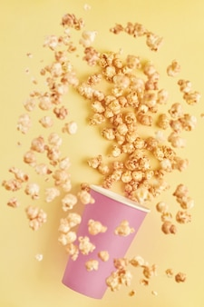 Flying delicious sweet popcorn with caramel in pink paper cup, isolated on trend color yellow table.