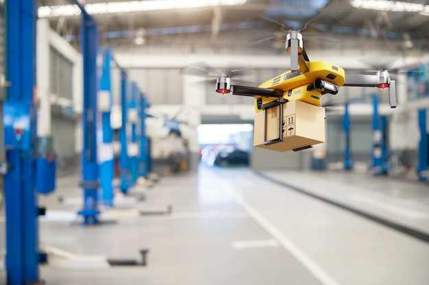 Flying delivery drone transferring parcel box from distribution warehouse to automotive garage customer service center background. modern innovative technology and gadget concept.