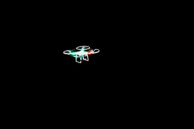 Flying drone on the black background