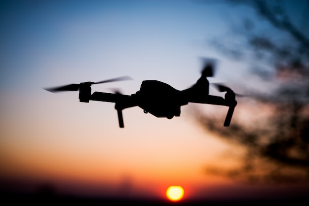 ドローンを夕日に飛ばします。太陽に対するシルエット。動きのクワッドヘリコプター。