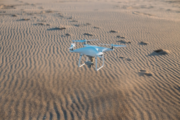 Flying drone landing on sand at beach