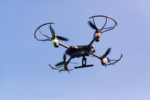 Летающий беспилотник или вертолет в голубое небо.