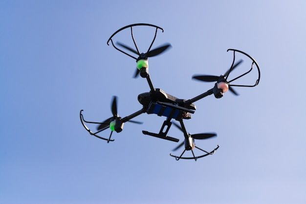 Flying drone or quad copter in blue sky.