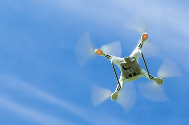 Flying drone quadcopter with digital camera on blue sky