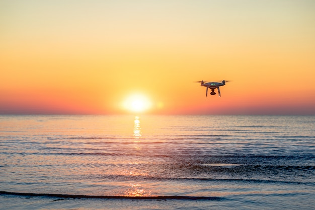 Flying drone on a sea sunset