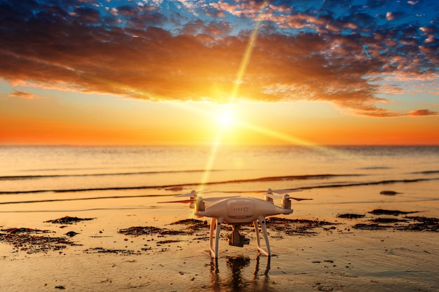 Flying drone on a  of sea sunset