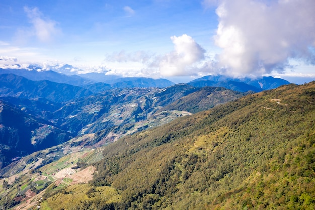 Flying drone towards beautiful amazing famous mt. hehuan in taiwan over above the hilltop, aerial view shot.