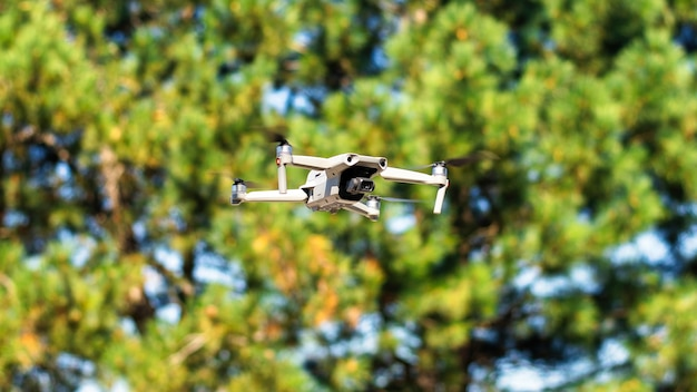 Flying drone with greenery on the background