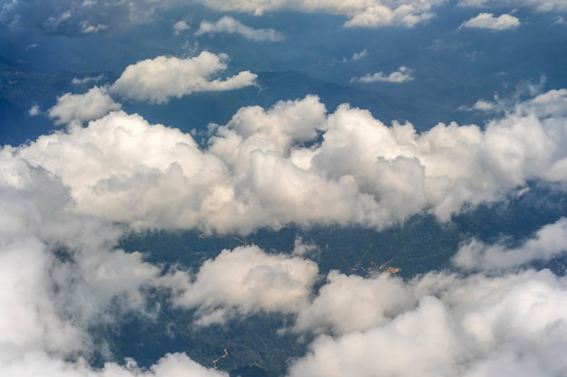 Flying above the earth and above the clouds in the territory of kota kinabalu, island borneo, malaysia. airplane window view. the plane flies in the sky above the earth.