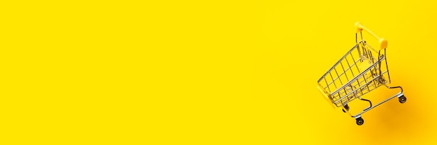 Flying empty shopping trolley on bright yellow background. close-up. banner.