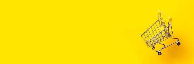Летающая пустая тележка для покупок на ярко-желтом фоне. крупный план. баннер.