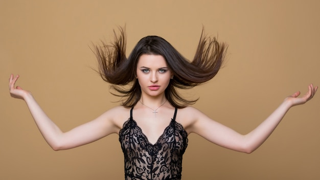 흐르는 머리카락을 비행. 섹시 한 검은 끈 콤보 죄수 복에 아름 다운 갈색 머리 소녀. 패션 란제리. 럭셔리 여자.