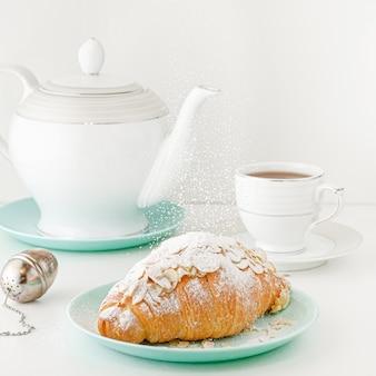 飛行食品のコンセプト。ティーポットと紅茶の白い朝食用テーブルで焼きたてのクロワッサンに落ちる粉砂糖。正方形の画像