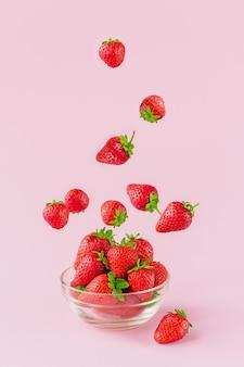 Летающая свежая клубника в прозрачной стеклянной миске. здоровая пища на светло-розовом фоне