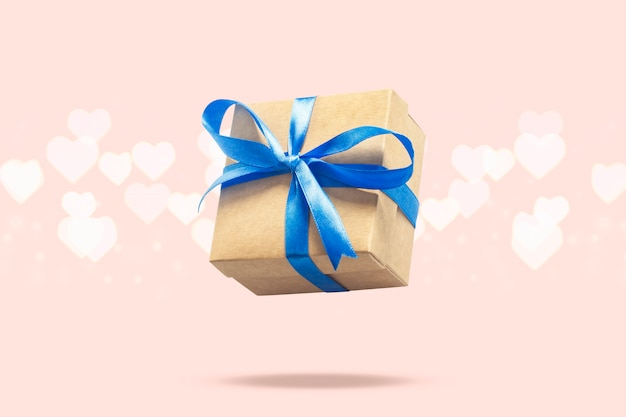 Flying gift box on a light pink surface with heart shaped bokeh. holiday concept, gift, sale, wedding and birthday.
