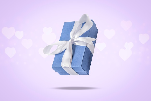 Flying gift box on a light surface with heart shaped bokeh. holiday concept, gift, sale, wedding and birthday.