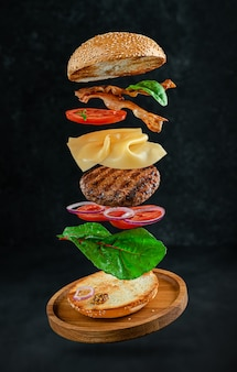 Flying hamburger with ingredients on dark stone surface