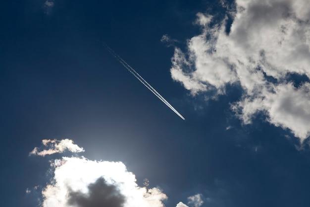 Высоко в небе летел самолет, за которым от двигателя оставался белый инверсионный след на фоне голубого неба и белых кучевых облаков.