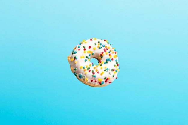 Полет в воздухе пончик с белой глазурью на синем. пекарня, концепция выпечки.