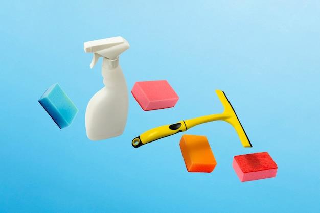 Полет в воздушном скребке, брызгах и губках для очистки и мытья на синем изолированном фоне. концепция очистки.