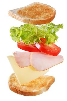 Летающие ингредиенты для бутерброда с беконом и овощами, изолированные на белом фоне