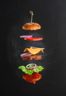 클래식 치즈 버거 참깨 번, 양파 링, 토마토 슬라이스 및 육즙이 풍부한 바베큐 커틀릿의 비행 재료. 검은 분필 보드 배경에 패스트 푸드의 레이어