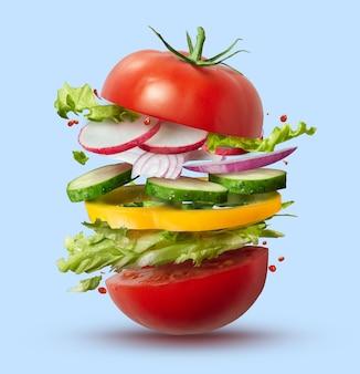 Летающие ингредиенты веганского бургера, изолированные на синем. идея концепции здорового питания.