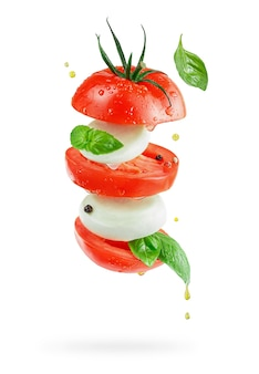 Flying italian salad caprese with mozzarella cheese, tomatoes and basil