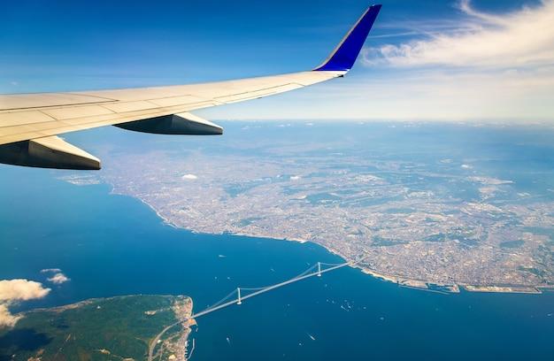 Flying above japan: view of the akashi kaikyo bridge through an airplane window