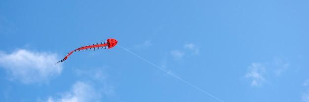 비행 연. 여러 가지 빛깔의 연이 하늘을 날고 있습니다. 구름과 태양이 있는 푸른 하늘. 텍스트 또는 복사 공간을 위한 공간입니다.